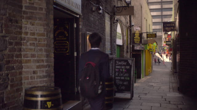 Shot of a narrow alley in Dublin, Ireland with a pub and other shops along it. People walk down the alley