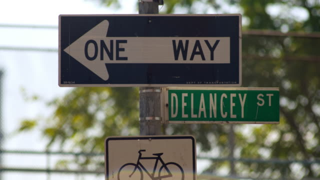 shot of a one way sign and the delancy street sign in new york city - one way stock videos & royalty-free footage