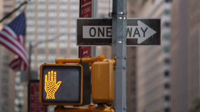 shot of a pedestrian crossing sign, changing from 'stop to 'go' in downtown manhattan, ny - segnaletica stradale video stock e b–roll