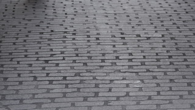 shot of a pedestrian walking down a cobbled street in paris, france - stone material stock videos & royalty-free footage