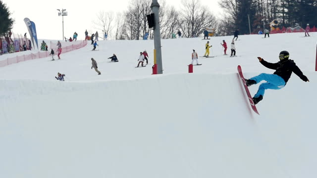 shot of a person snowboarding on halfpipe at ski resort - halfpipe stock-videos und b-roll-filmmaterial