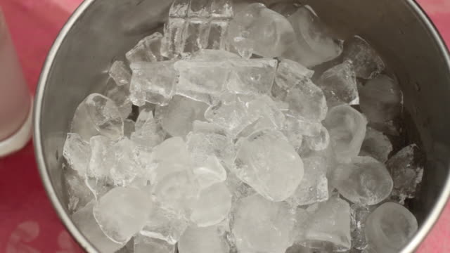 shot of a person using tongs to pick up pieces of ice from a bucket. - cooler container stock videos and b-roll footage