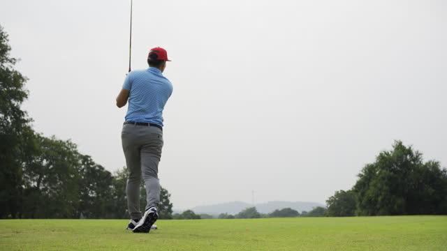 stockvideo's en b-roll-footage met ontsproten van een professionele aziatische mannelijke golfer die een teeschot op een golfcursus uitvoert. - opteeën