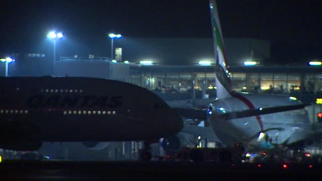 Shot of a Qantas aircraft being towed slowly on tarmac at night at Heathrow Airport London