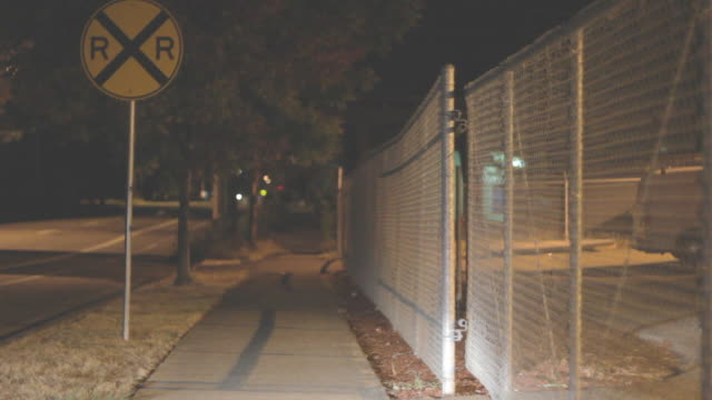 Shot of a sidewalk next to a chain linked fence and road sign.  Shot at night.