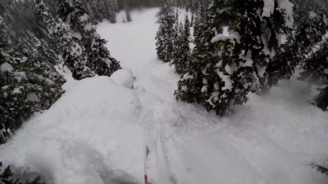 POV shot of a skier jumping a cliff in deep powder snow in the rocky mountains - 4k