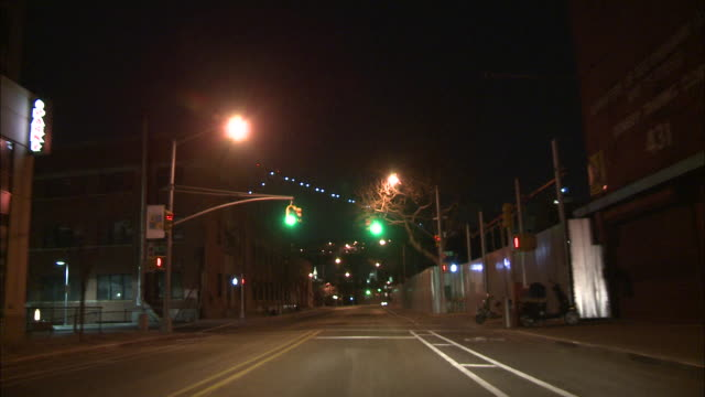 A POV shot of a street and an industrial area as taken from a moving vehicle at night.