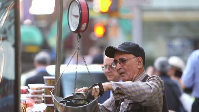 Shot of a street vendor weighing grapes on scales in Downtown Manhattan NY
