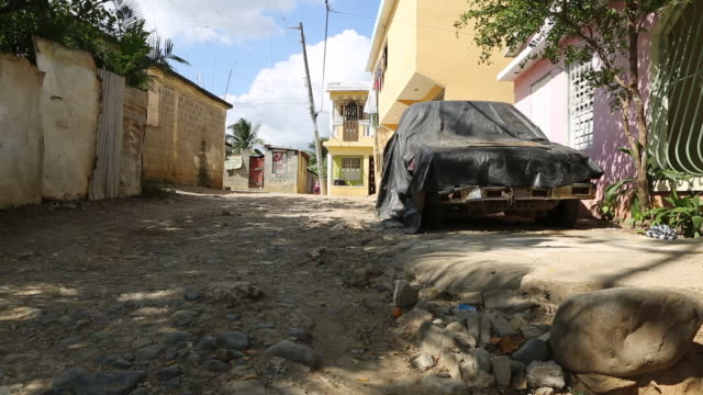 santa domingo dominican republic november 29 2012 shot of a street with a broken road and a probably broken and covered car in the poor neighbourhood... - santo domingo dominican republic stock videos & royalty-free footage