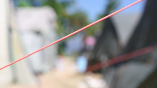 shot of a string that is stabilising a tent at the refugee camp in port-au-prince, haiti which was founded in 2010 after the devastating earthquake. - アフリカ系カリブ人点の映像素材/bロール