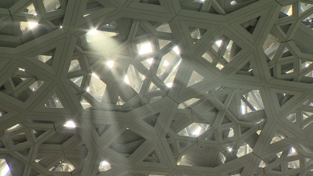 Shot of a sunbeam shining through the roof of the Louvre in Abu Dhabi and illuminating the floating dust