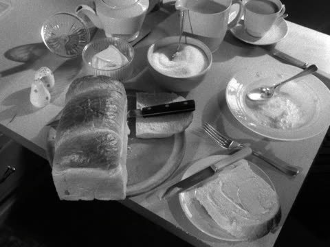 Shot of a table laid out for breakfast A person starts to butter a piece of bread An empty bowl is taken away from the table and replaced by a plate...