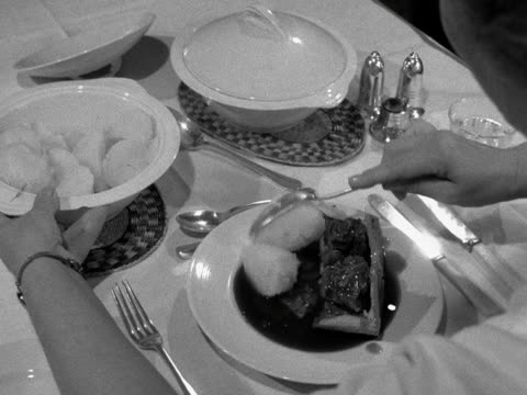 vídeos de stock, filmes e b-roll de shot of a table laid out for dinner with a plate of meat pie a person starts to help themselves to boiled potatoes and carrots from two serving dishes - toalha de mesa