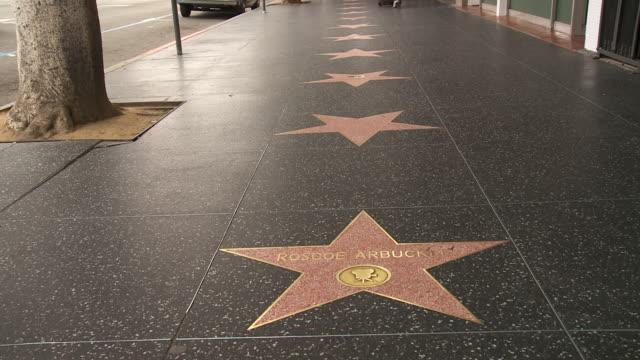 vídeos de stock e filmes b-roll de shot of a the roscoe arbuckle star on the hollywood boulevard walk of fame.  people walk past - passeio da fama de hollywood