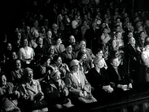 Shot of a theatre audience laughing and occasionally clapping during a performance 1958 NB scratches visible on film print