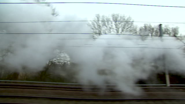 POV shot of a trail of steam passing by a window on the Flying Scotsman as it travels through the English countryside