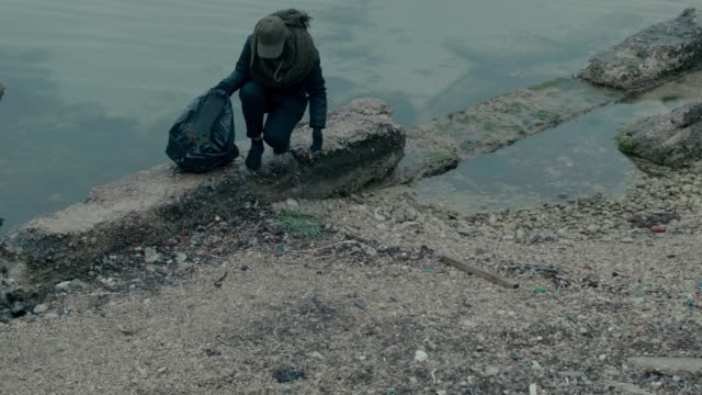 shot of a volunteer crouching against the shores of sevastopol crimea picking up small pieces of litter - sevastopol crimea stock videos and b-roll footage