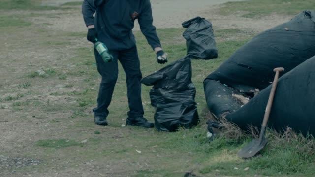 shot of a volunteer picking up plastic soda bottles in a littered area in sevastopol crimea - sevastopol crimea stock videos and b-roll footage