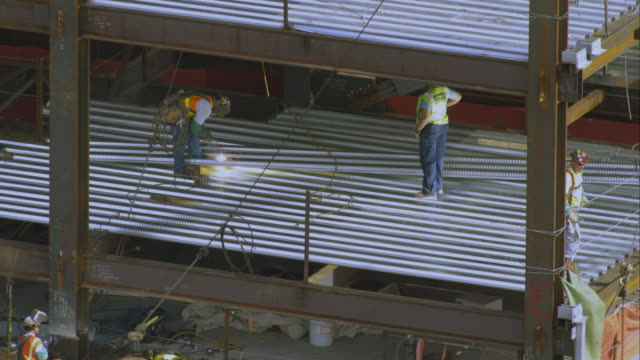shot of a welder and other workers on a building. - girder stock videos & royalty-free footage