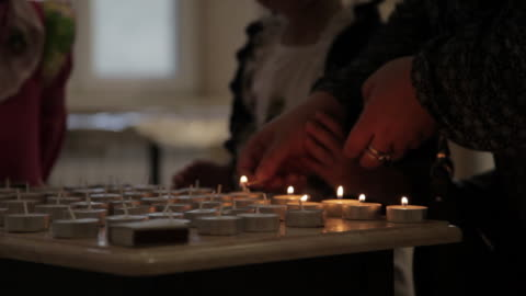 shot of a woman and two young girls lighting tea lights in a synagogue. - judaism stock videos & royalty-free footage