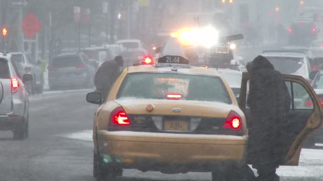 shot of a woman entering the backseat of a taxi in new york city on a snowy day - slippery stock videos & royalty-free footage