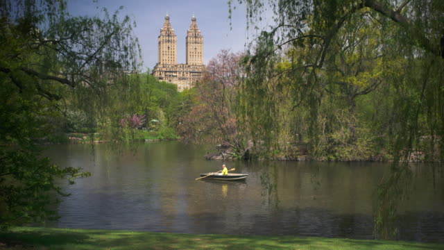 shot of a woman in a rowboat on the lake in central park, manhattan on a sunny day.  the towers of the san remo apartments can be seen in the skyline - マンハッタン セントラルパーク点の映像素材/bロール