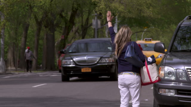 shot of a woman trying and failing to hail a cab near central park in manhattan. - yellow taxi点の映像素材/bロール