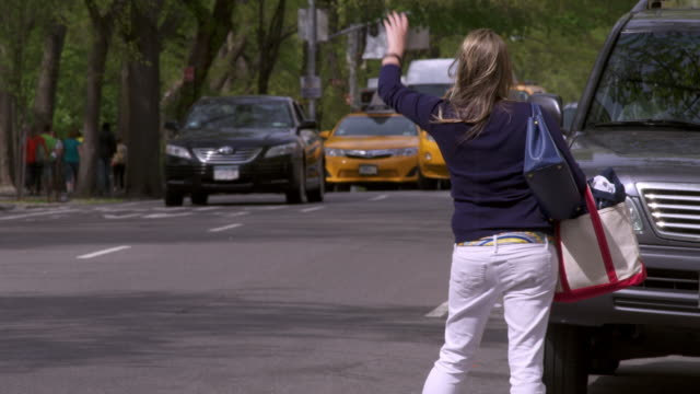 shot of a woman trying and failing to hail a cab near central park in manhattan. - 腕を上げる点の映像素材/bロール