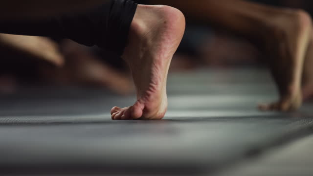 shot of a woman's foot as she and other women around her participate in yoga at an exercise studio - barefoot stock videos & royalty-free footage