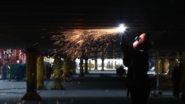 shot of a worker welding at the shipyard of hyundai samho heavy industries corporation - schiffswerft stock-videos und b-roll-filmmaterial