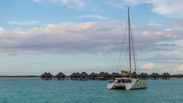 shot of a yacht on the sea and bungalow - insel tahiti stock-videos und b-roll-filmmaterial