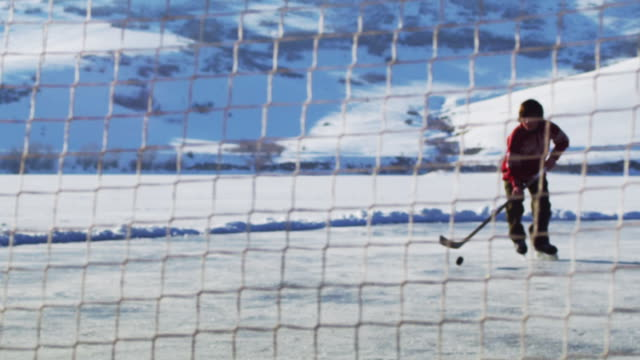 shot of a young boy through a hockey net as he prepares to dribble forward and score in slow motion.  he is outdoors and surrounded by mountains. - sports activity stock videos & royalty-free footage