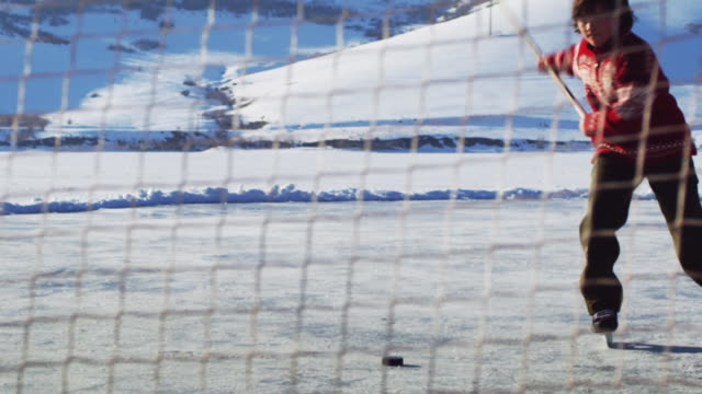 shot of a young boy through hockey net as he dribbles forward and shoots then slides and falls down.  he is outdoors and surrounded by snow covered mountains. - ユタ州 パークシティ点の映像素材/bロール