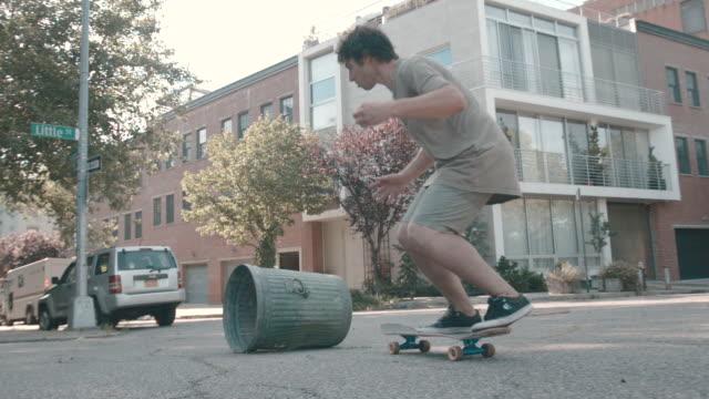 vídeos de stock, filmes e b-roll de a shot of a young man skateboarding through the streets of brooklyn, nyc - escrita ocidental