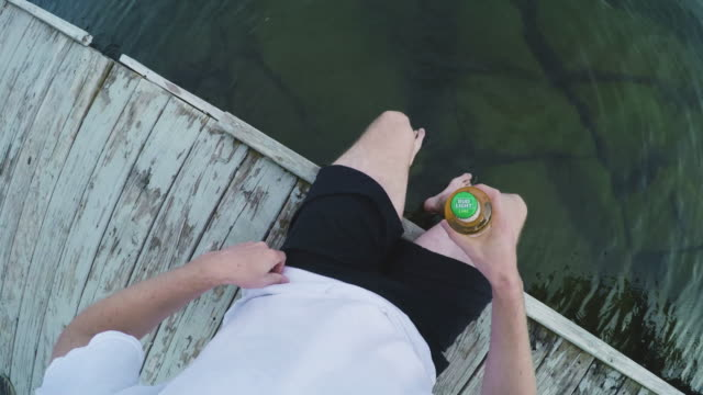 A POV shot of a young, White Male drinking a beer on the dock - 4k