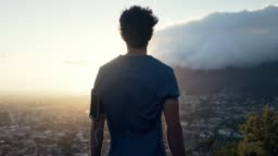 Shot of a young white male facing backwards at the camera and overlooking the view of the city and nature at sunrise