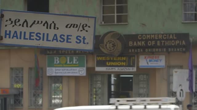 ms tu shot of across street of bank of ethiopia with armed guard outside sitting, holding his ak-47 / addis abbaba, ethiopia - アジスアベバ点の映像素材/bロール