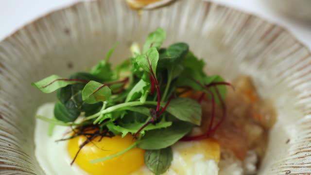 ecu pan shot of adding sesame oil into bibimbap (korea's traditional food) / seoul, south korea - gesunde ernährung stock-videos und b-roll-filmmaterial