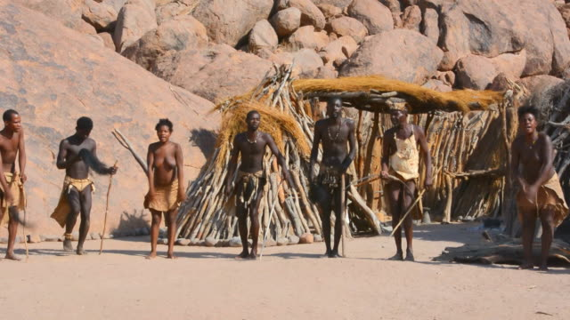 stockvideo's en b-roll-footage met ms pan shot of africa damara tribe traditional life in living museum dancing tribe audio / damaraland, namibia, south africa  - inheemse cultuur
