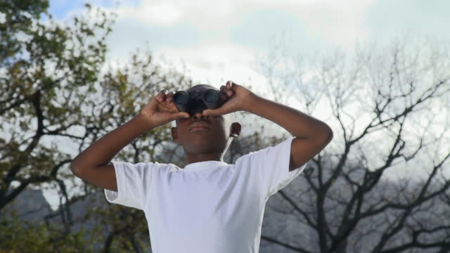 ms la shot of african boy looking through binoculars in garden / cape town, western cape, south africa - binoculars stock videos & royalty-free footage