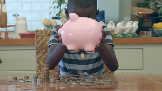 MS Shot of African boy playing with coins in piggy bank / Cape Town, Western Cape, South Africa