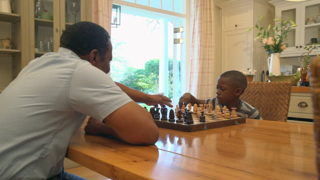 ms pan shot of african child being taught to play chess by grandparent / cape town, western cape, south africa - chess stock videos & royalty-free footage