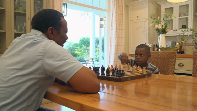 MS PAN Shot of African child being taught to play chess by grandparent / Cape Town, Western Cape, South Africa