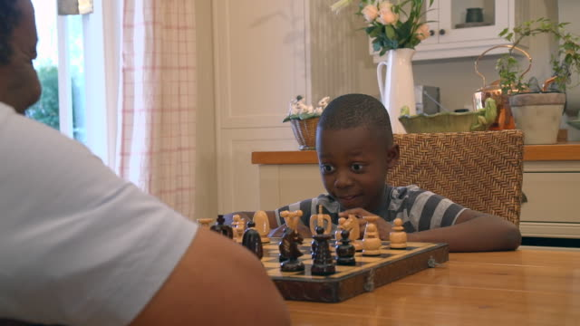 ms pan shot of african child being taught to play chess by grandparent / cape town, western cape, south africa - board game stock videos & royalty-free footage
