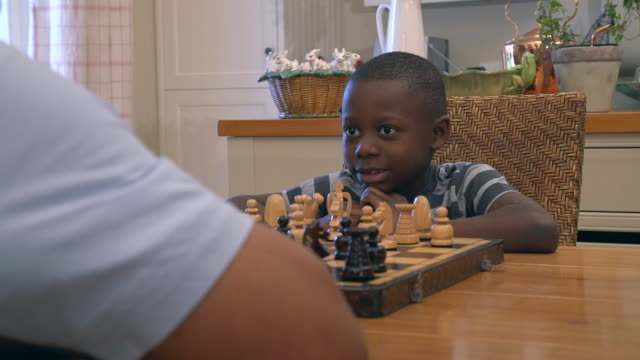 ms pan shot of african child being taught to playing chess by grandparent / cape town, western cape, south africa - チェス点の映像素材/bロール