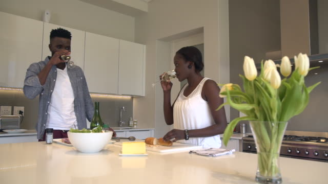 ms pan shot of african couple cooking and preparing food in kitchen / cape town, western cape, south africa - french food wine stock videos & royalty-free footage