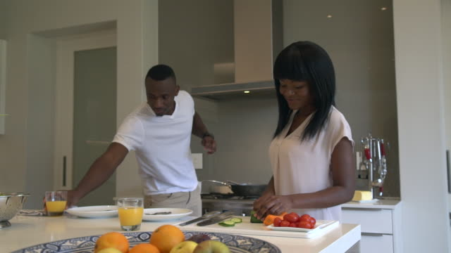 ms zi shot of african couple preparing and cooking food in kitchen / cape town, western cape, south africa - detox stock videos & royalty-free footage
