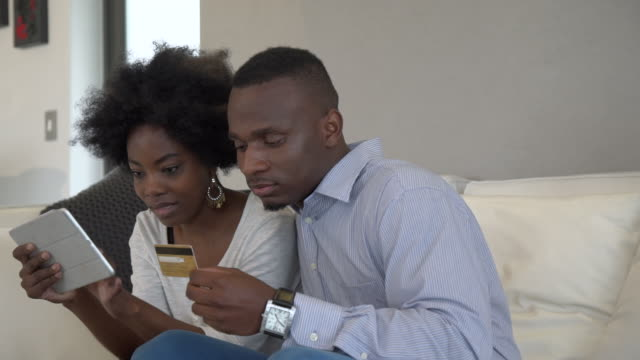 MS PAN Shot of African couple using digital tablet and credit card to shop online/ Cape Town, Western Cape, South Africa