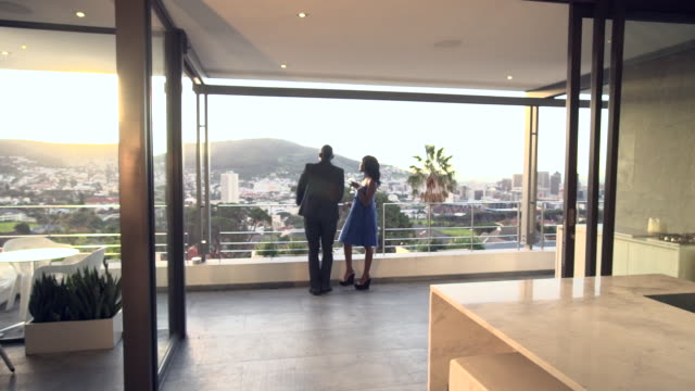 WS ZI PAN Shot of African couple walking out to balcony from kitchen / Cape Town, Western Cape, South Africa