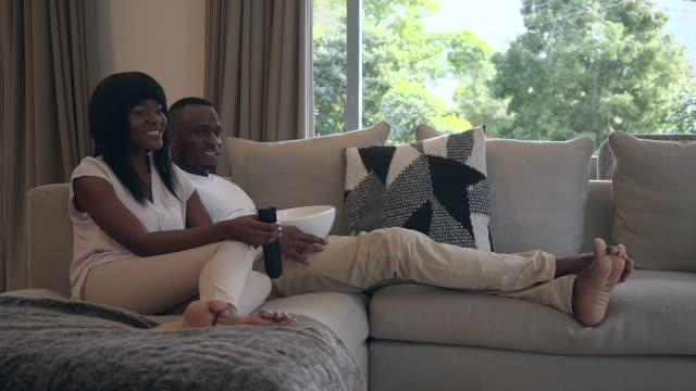 ms shot of african couple watching television / cape town, western cape, south africa - bowl stock videos and b-roll footage